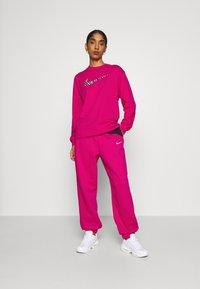 Nike Sportswear - Tracksuit bottoms - fireberry/black/white - 1