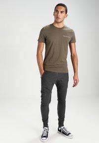 Tigha - TREVOR ZIP - Pantalones deportivos - vintage grey - 1