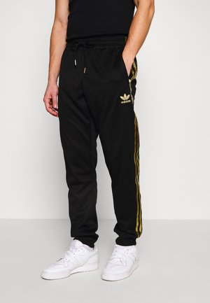 SUPERSTAR 3STRIPES TRACK PANTS - Tracksuit bottoms - black/gold