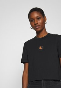 Calvin Klein Jeans - BADGE CROPPED TEE - T-shirt basique - black