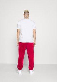 Karl Kani - SIGNATURE TRACK PANTS UNISEX - Pantaloni sportivi - dark red - 2