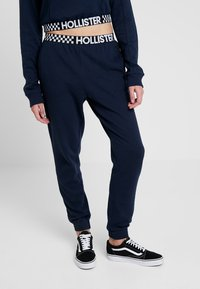 Hollister Co. - HIGH RISE JOGGER WITH LOGO ELASTIC BAND - Tracksuit bottoms - navy - 0