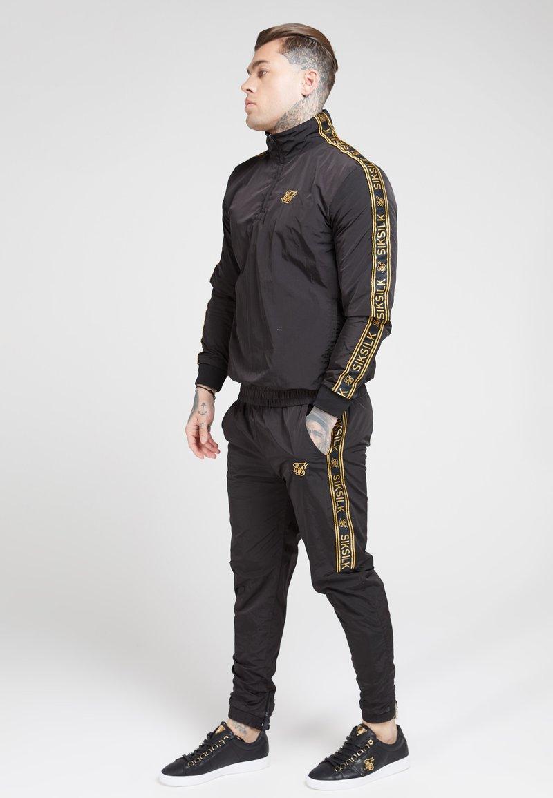 SIKSILK - QUARTER ZIP FUNNEL TAPE OVERHEAD - Summer jacket - black/gold
