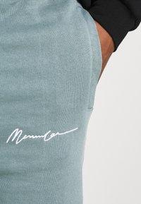 Mennace - UNISEX ESSENTIAL SIGNATURE  - Tracksuit bottoms - dark green - 4