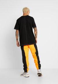 adidas Originals - REVEAL YOUR VOICE TRACKPANT - Tracksuit bottoms - flash orange - 2