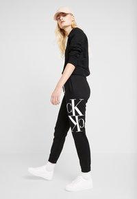 Calvin Klein Jeans - MIRRORED MONOGRAM PANT - Teplákové kalhoty - black - 1