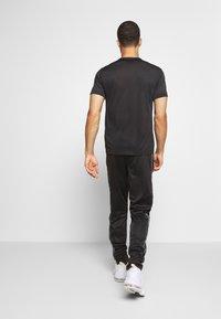Champion - LEGACY TAPE CUFF PANTS - Pantalon de survêtement - black - 2