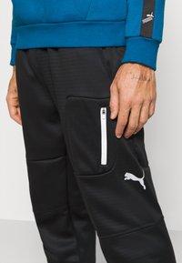Puma - EVOSTRIPE WARM PANTS - Pantalon de survêtement - black - 4