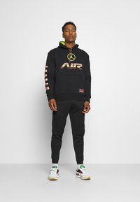 Nike Sportswear - TRIBUTE - Tracksuit bottoms - black/white - 1