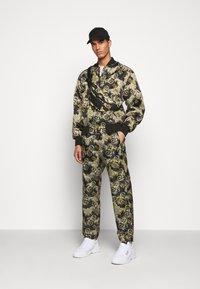 Versace Jeans Couture - RISTOP LOGO BAROQUE - Pantaloni sportivi - nero - 1