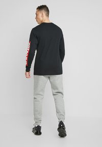 Nike Sportswear - CLUB PANT - Trainingsbroek - dark grey heather