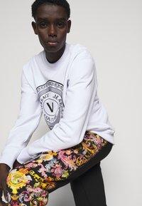 Versace Jeans Couture - HEAVY PRINT VERSAILLES - Tracksuit bottoms - black - 4