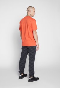 adidas Originals - TREFOIL MONOGRAM GRAPHIC SPORT PANTS - Spodnie treningowe - black - 2
