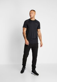 Hummel - HMLISAM REGULAR - Tracksuit bottoms - black - 1
