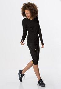 Skins - DNAMIC - 3/4 sports trousers - black/limoncello - 1
