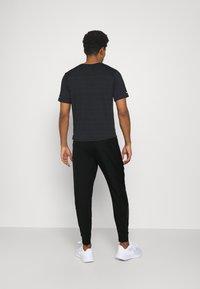 Nike Performance - Tracksuit bottoms - black - 2