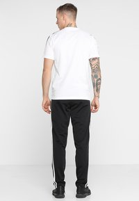 adidas Performance - 3 STRIPES SPORTS REGULAR PANTS - Träningsbyxor - black/white - 2