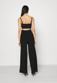 NA-KD - NA-KD X ZALANDO EXCLUSIVE SOFT RIBBED PANTS - Trousers - black - 2
