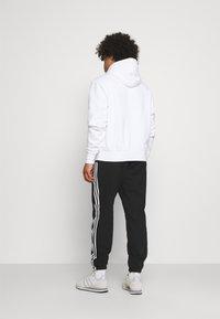 adidas Originals - NINJA PANT UNISEX - Tracksuit bottoms - black - 2