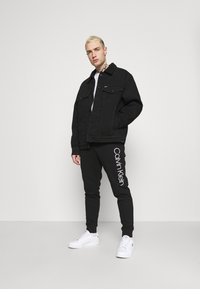 Calvin Klein - LOGO PANTS - Tracksuit bottoms - black - 1