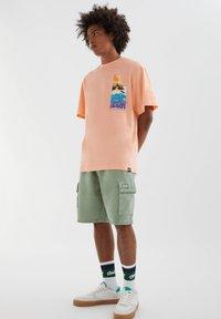 PULL&BEAR - MIT FARBLICH ABGESETZTEM SLOGAN - Print T-shirt - orange - 1