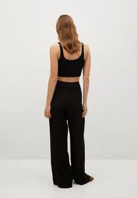 Mango - FLUIDO PLISADO - Trousers - black - 2