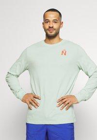 Nike Performance - DRY TEE TRAIL - Camiseta de deporte - pistachio frost - 0