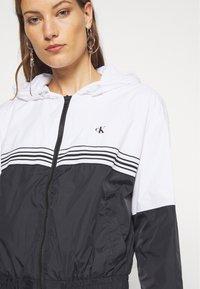 Calvin Klein Jeans - STRIPE TAPE HOODED WINDBREAKER - Summer jacket - black - 5