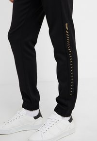 BOSS - HADIKO WIN - Pantaloni sportivi - black/gold