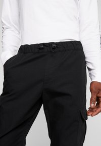 Urban Classics - RIPSTOP CARGO PANTS - Cargo trousers - black - 4