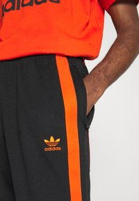 adidas Originals - WARMUP - Tracksuit bottoms - black/corang - 4