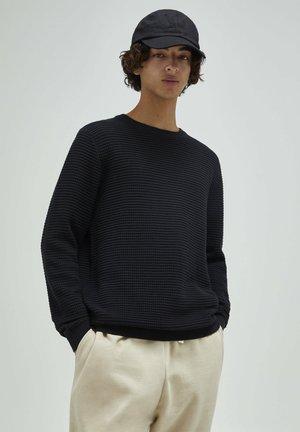 Stickad tröja - mottled black