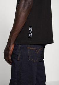 Versace Jeans Couture - LOGO - T-shirt imprimé - black - 7