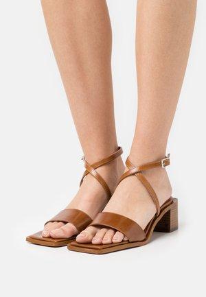Sandaalit nilkkaremmillä - cognac poncho
