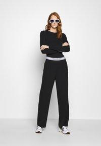 Calvin Klein Jeans - LOGO ELASTIC DRAPEY PANT - Spodnie materiałowe - black - 1