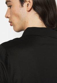KARL LAGERFELD - PRESS BUTTON - Polo shirt - black - 4
