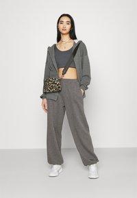 NA-KD - NA-KD X ZALANDO EXCLUSIVE - LOOSE FIT PANTS - Tracksuit bottoms - dark grey - 1