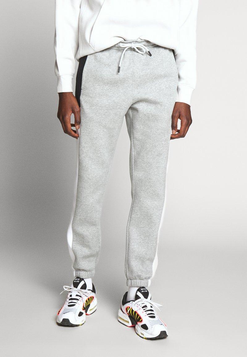 Nike Sportswear - Tracksuit bottoms - dark grey heather/white/black