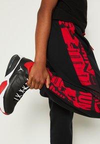 Jordan - ESSENTIALS - Tracksuit bottoms - gym red/black - 4