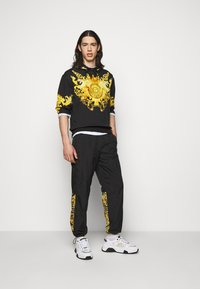 Versace Jeans Couture - CRINKLE  - Tracksuit bottoms - black - 1