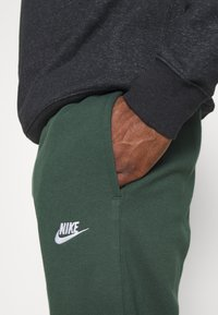Nike Sportswear - CLUB PANT - Tracksuit bottoms - galactic jade/white - 6
