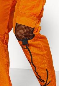 Karl Kani - SIGNATURE CRINCLE PANTS UNISEX - Pantalon cargo - orange - 3
