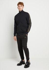 HUGO - DOAK - Teplákové kalhoty - black / gold - 1