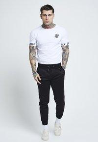 SIKSILK - Pantalon de survêtement - black/gold - 1