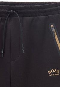 BOSS - HALBOA - Spodnie treningowe - black/gold - 5