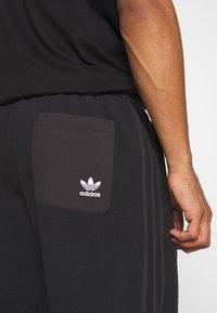 adidas Originals - UNISEX - Tracksuit bottoms - black - 4
