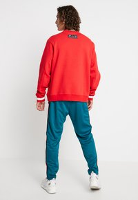 Nike Sportswear - PANT TRIBUTE - Tracksuit bottoms - geode teal/university red - 2