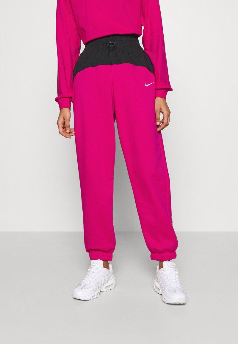Nike Sportswear - Tracksuit bottoms - fireberry/black/white