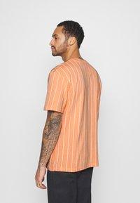 Karl Kani - SMALL SIGNATURE PINSTRIPE TEE UNISEX - Print T-shirt - coral/white - 3