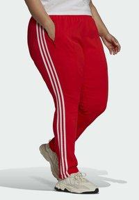 adidas Originals - PRIMEBLUE SST - Tracksuit bottoms - red - 4